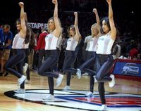 Clipper Spirit Dancers Raise their left arms in white top and black pants at Staples Center 2016